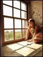 Девушка сидит у окна и смотрит в даль, ожидая возвращения получателя открытки.