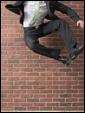 Молодой человек в костюме подпрыгнул вверх на фоне кирпичной стены: очень жду окончания рабочего дня.