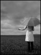 Молодая девушка одиноко стоит посреди поля, ожидая своего друга, который не пришёл на встречу из-за дождя.