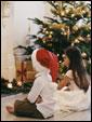 мальчик и Девочка сидят у камина, рядом с Новогодней елкой.